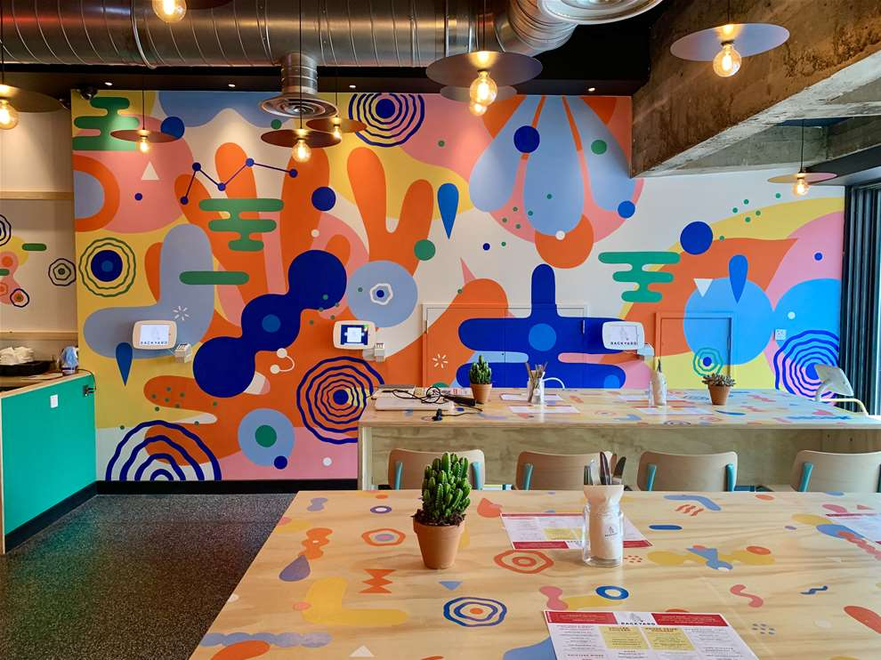 Anna Higgie, Bold, colourful geometric handpainted mural in a café