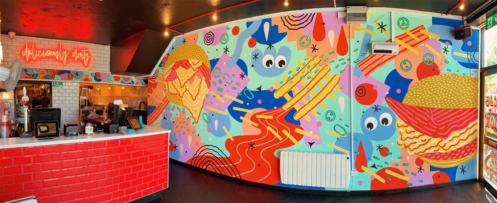 Anna Higgie, Bold, colourful geometric handpainted mural in a burger restaurant. Illustration of burger and fries