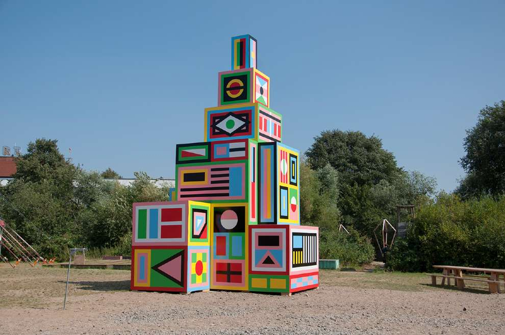 Kitra, Bold and colourful geometric shapes design hand painted on a wooden sculpture