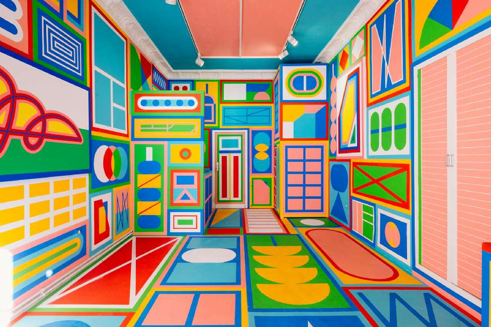 Kitra, Bold and colourful geometric shapes design hand painted on 4 walls, ceiling and floor of a room