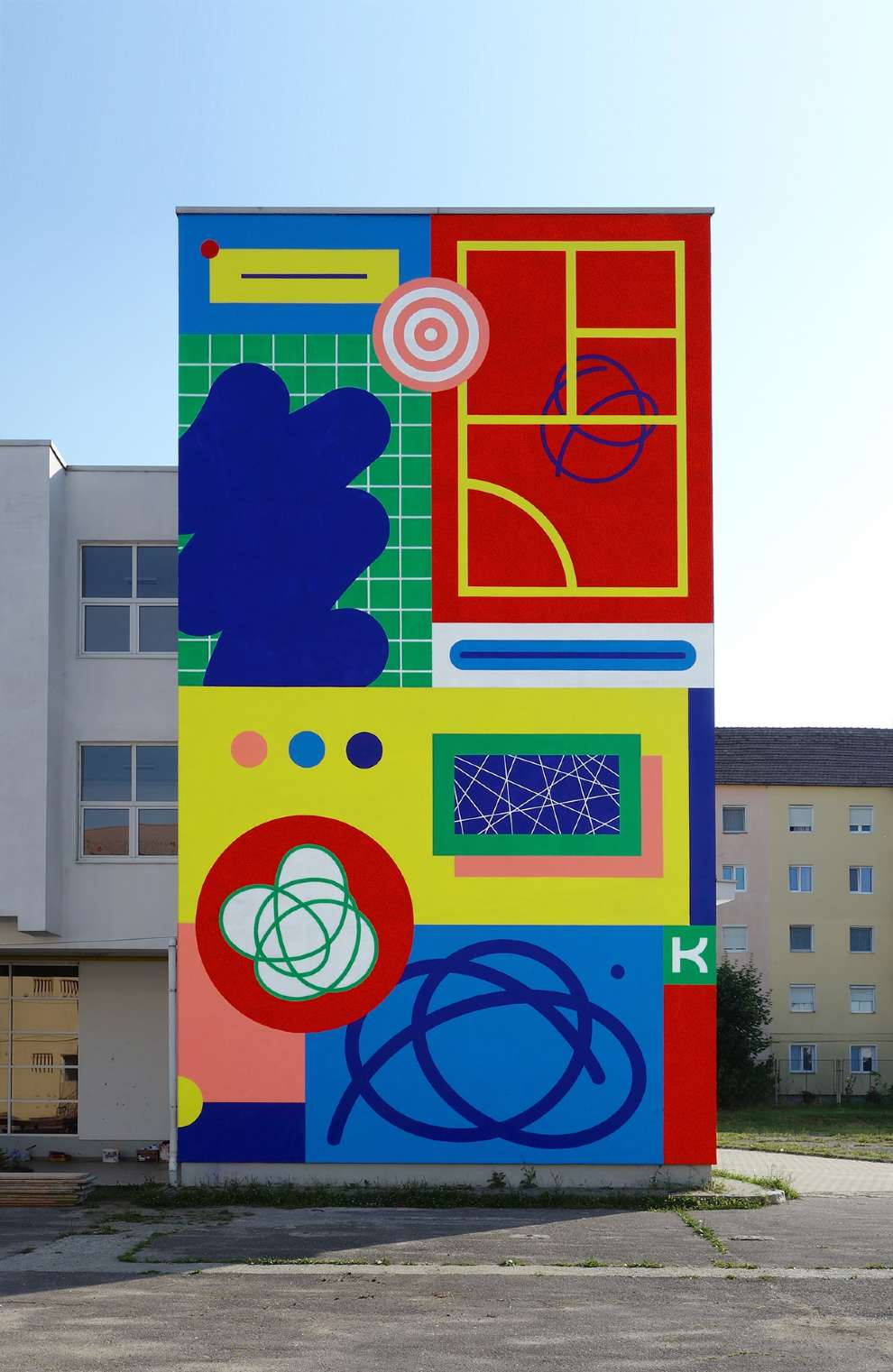 Kitra, Bold and colourful geometric shapes design hand painted on a building facade