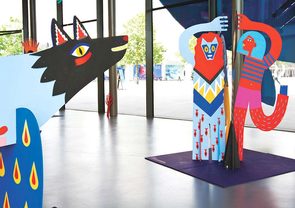 Margaux Carpentier, Wood sculpture of a wolf, a women and other creature, hand painted in bright and bold colours