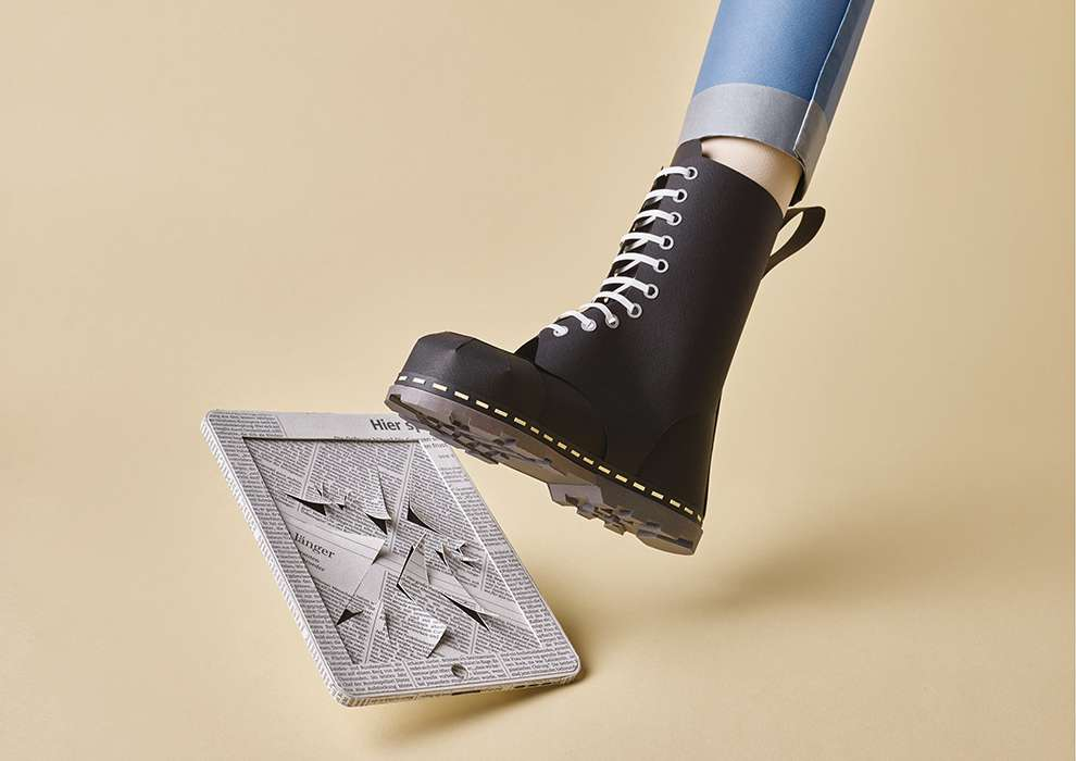 WRK, Papercraft illustration of a boots walking on an Ipad made of newspaper