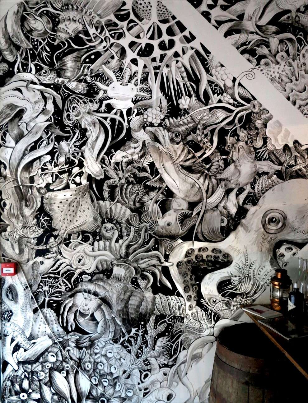 Good Wives & Warriors, black and white hand painted pub mural of a sea scene with sea creatures and fishes